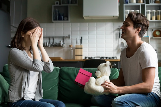 Loving husband closing eyes of wife presenting romantic surprise gift Free Photo