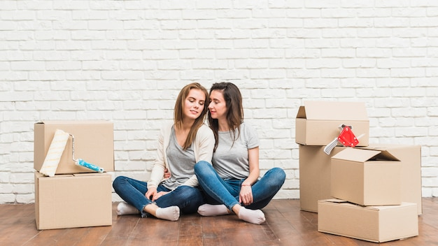Loving lesbian young couple sitting on hardwood floor with moving cardboard boxes in their new house Free Photo