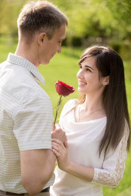 loving man giving a rose to his girlfriend photo free. Black Bedroom Furniture Sets. Home Design Ideas