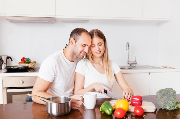 Loving man sitting with his wife cutting the vegetables with knife Free Photo