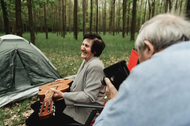 Влюбленная пара зрелых, приезжающих на пикник с гитарой. счастливая пара старших играет на гитаре и романтическое свидание в лагере. Premium Фотографии