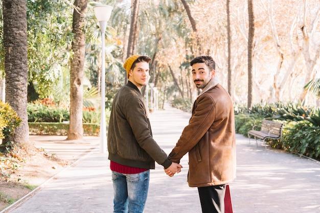 Loving men holding hands posing in park Premium Photo
