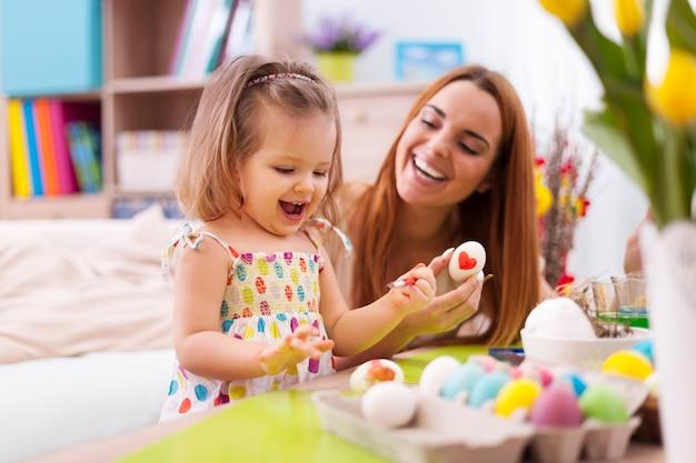 愛情深い母親と赤ちゃんがイースターエッグを描く 無料写真