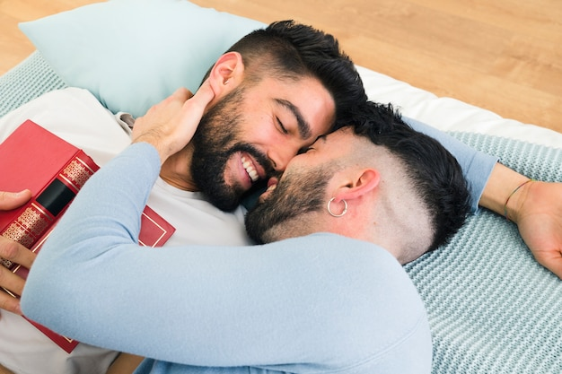 Loving romantic young gay couple lying on bed Free Photo