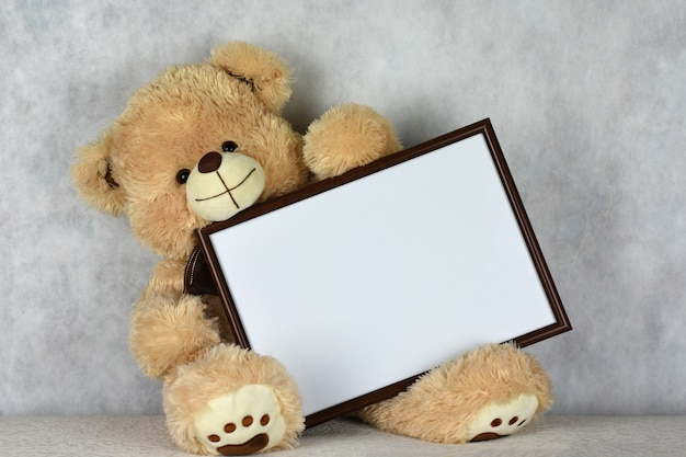A loving teddy bear keeps a frame with a heart on the day of saint valentine's day Premium Photo