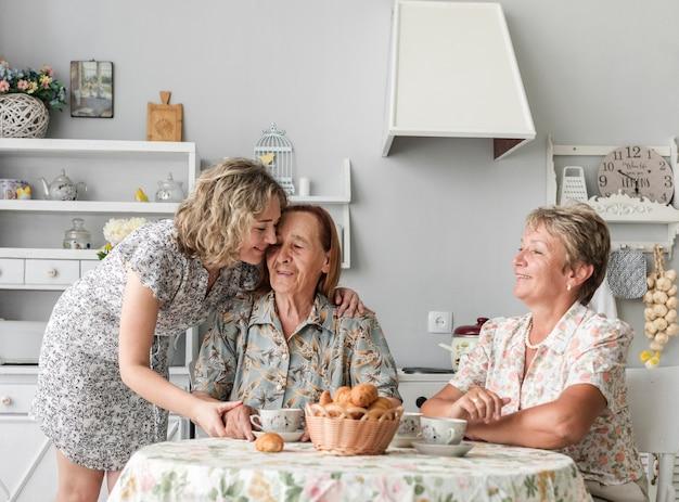 Loving three generation women having breakfast together Free Photo