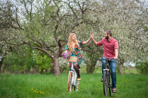 Loving young couple riding bicycles in the spring garden Premium Photo