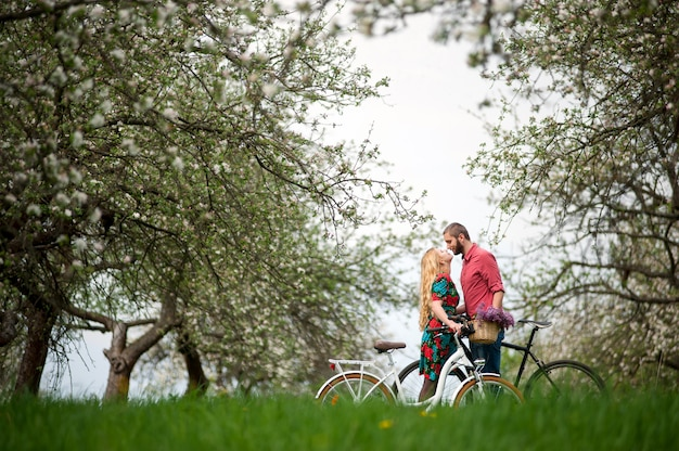 Loving young couple with bicycles in spring garden Premium Photo