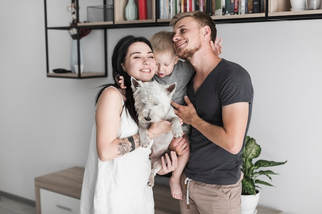 Loving young couple with their cute son and white dog at home Free Photo
