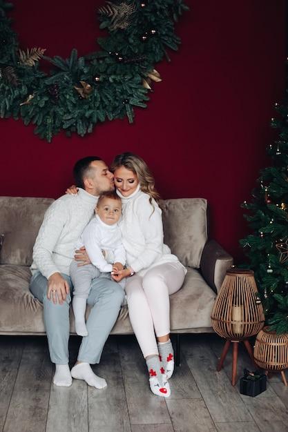 ソファに座って子供を抱きしめながらキスをする愛情のある若い親 無料写真