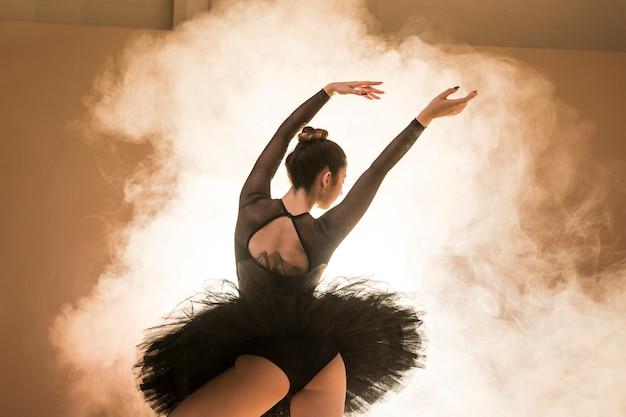 Low angle ballerina posing in smoke Free Photo