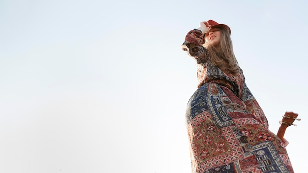 Low angle of bohemian woman with copy space and ukulele Free Photo