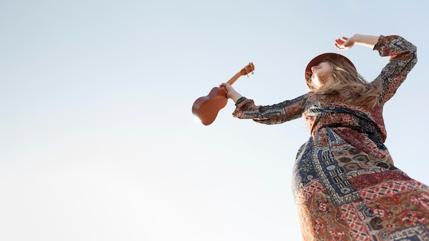 Low angle of bohemian woman with ukulele and copy space Free Photo