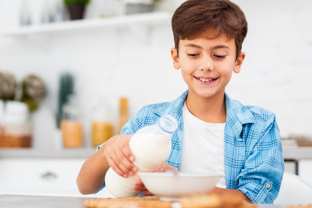 Low angle boy preparing cereals with milk Free Photo