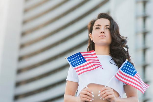 Низкий угол брюнетка женщина держит два флага сша Бесплатные Фотографии
