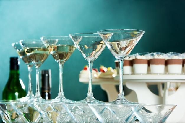 Низкий угол крупным планом выстрел из бокалов мартини на партийном столе в ресторане посуда стеклянная посуда алкоголь праздничный праздник напитки напитки настроение. Бесплатные Фотографии