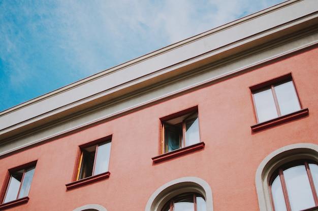 Низкий угол крупным планом выстрел из розового здания с окнами Бесплатные Фотографии