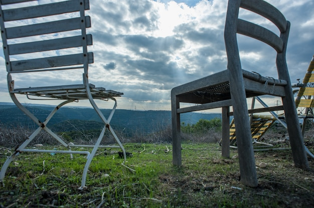 Низкий угол съемки стульев на улице под темным облачным небом Бесплатные Фотографии