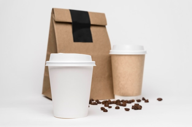 Low angle coffee cups and paper bag Free Photo