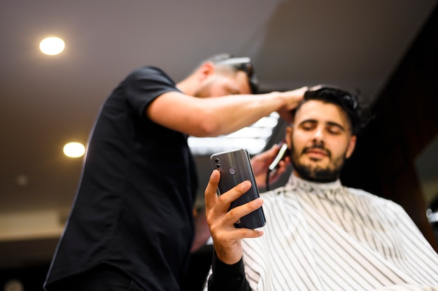 Low angle costumer at barber shop checking his phone Free Photo