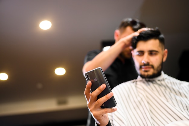Low angle costumer at barber shop looking at phone with copy space Free Photo