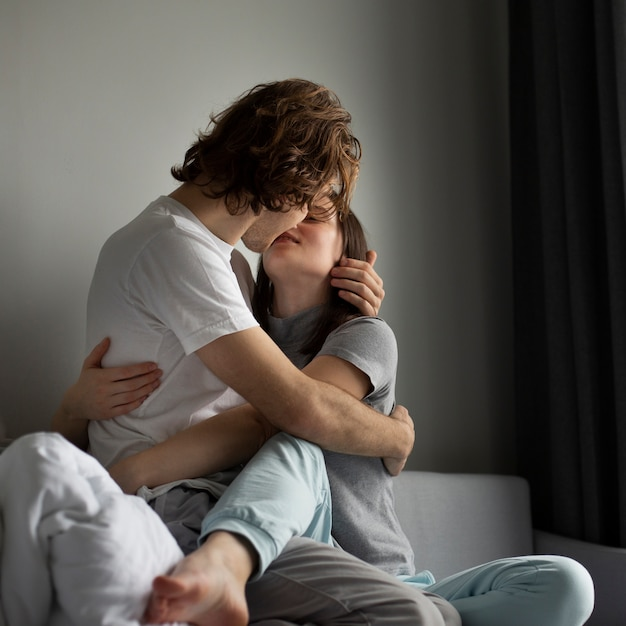 Low angle of couple kissing while cuddling | Free Photo