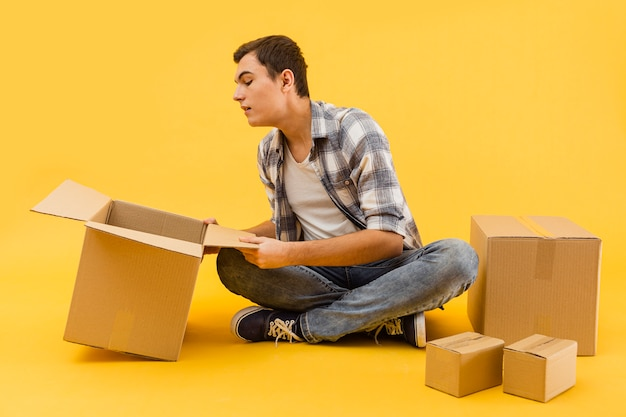 Low angle delivery man checking packaging boxes Free Photo