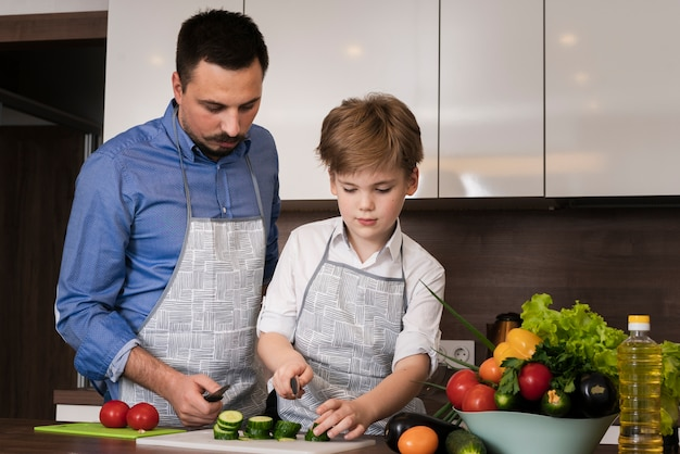 Low angle father teaching son to cut vegetables Free Photo