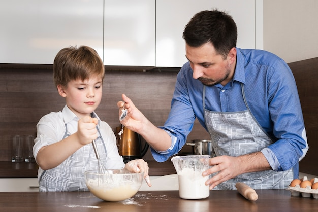 Low angle father teaching son to make dough Free Photo