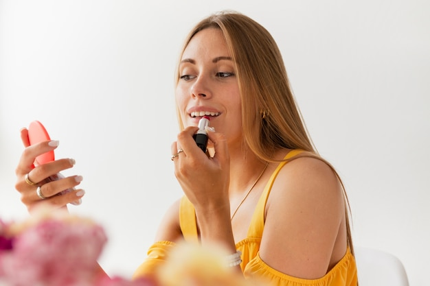 Low angle female blogger putting on lip gloss Free Photo