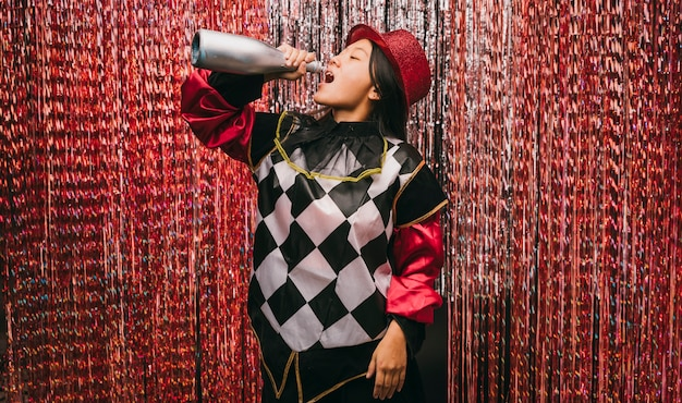 Low angle female in costume with champagne bottle Free Photo