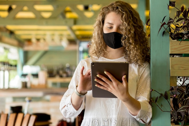 Low angle female with mask using tablet Free Photo