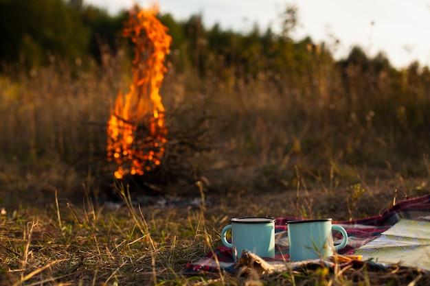 Низкий угол пламени огня с чашками рядом Бесплатные Фотографии