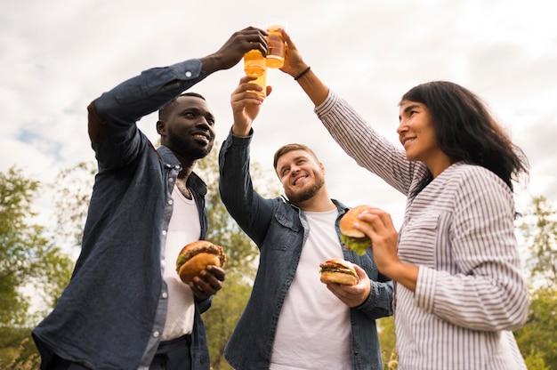ビールで乾杯するローアングルの友達 無料写真
