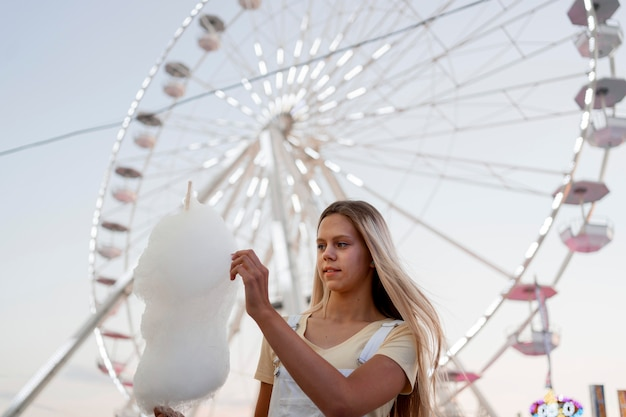 Zucchero filato della holding della ragazza di angolo basso Foto Gratuite