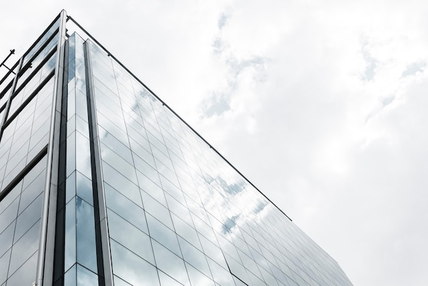 Low angle glass building with clouds Free Photo