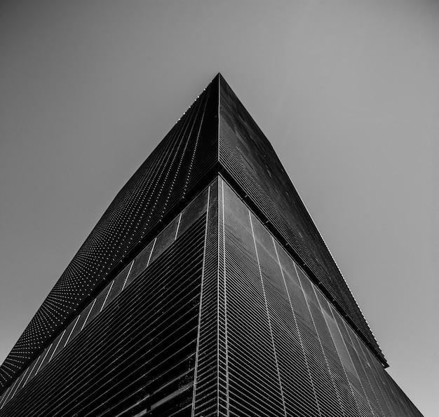 Colpo in scala di grigi di angolo basso di un edificio aziendale Foto Gratuite