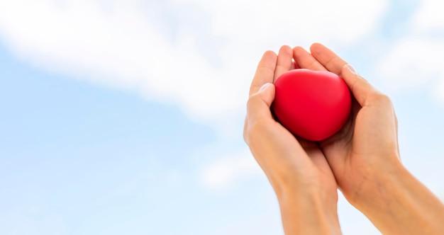 Basso angolo di mani che tengono a forma di cuore con copia spazio Foto Gratuite