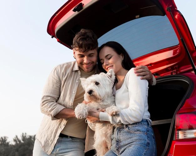 Низкий угол счастливая пара держит собаку Бесплатные Фотографии