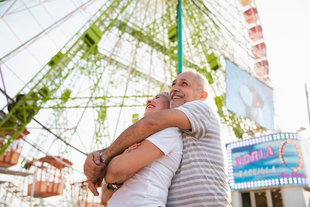 Low angle happy couple hugging near ferris wheel Free Photo