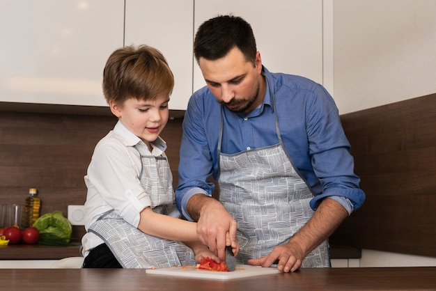 Low angle little boy in kitchen with father Free Photo