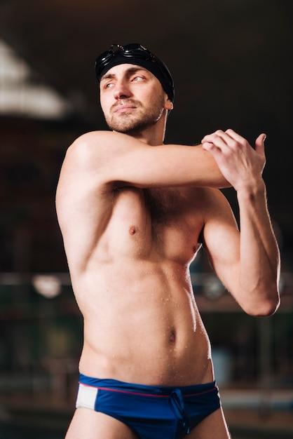 Allungamento maschio del nuotatore di angolo basso Foto Gratuite