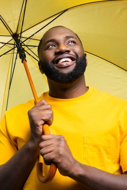Uomo basso angolo con ombrello Foto Gratuite