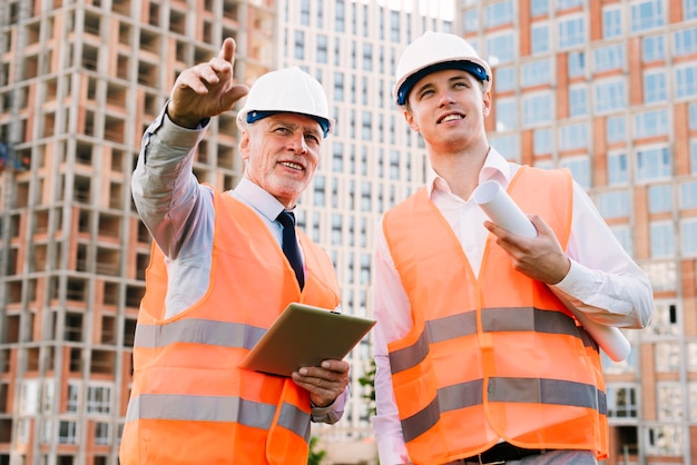 Low angle men with safety vests Free Photo