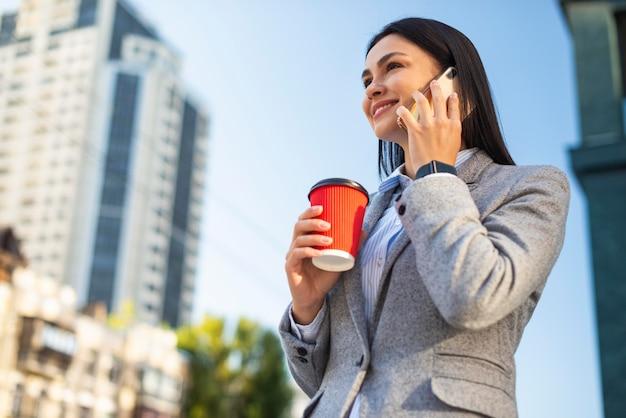 屋外でコーヒーを飲みながら電話で話している笑顔の実業家の低角度 無料写真