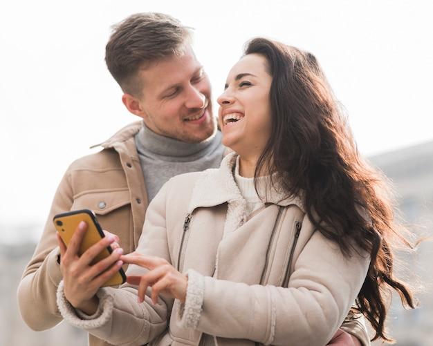 Низкий угол смайлик пара держит смартфон Бесплатные Фотографии