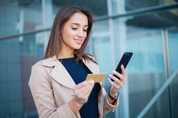 Low angle of pleased girl standing at the airport hall. he is using gold credit card and cellphone for paying Premium Photo
