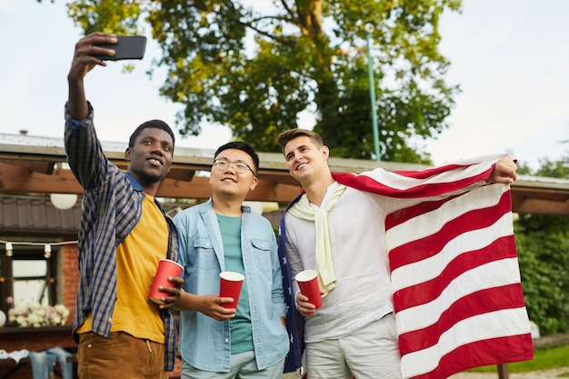 Low angle portrait of multi-ethnic group of taking selfie while enjoying outdoor party in summer for independence day Premium Photo