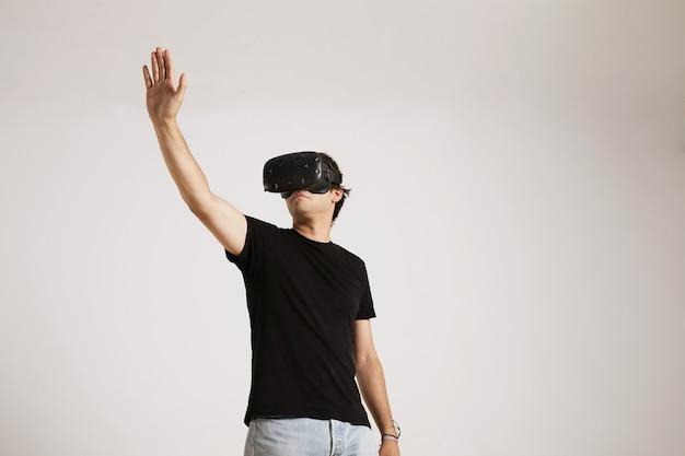 Ritratto di angolo basso di un giovane modello caucasico in jeans e maglietta nera senza etichetta che allunga la mano mentre gioca con gli occhiali vr sul muro bianco. Foto Gratuite
