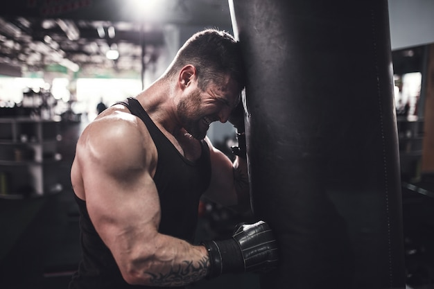 Low angle portrait of young tired sports man leaning on punching bag Premium Photo
